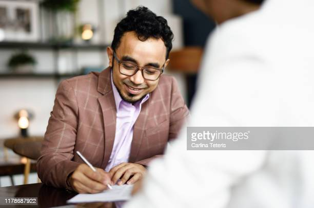 Malay man signing papers at a business meeting