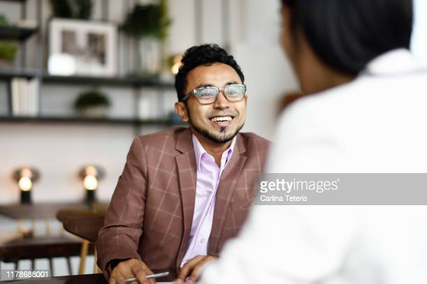 malay man signing papers at a business meeting - employee engagement stock pictures, royalty-free photos & images