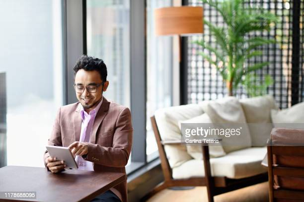 malay man working on a tablet in a co-working office - 30代の男性一人 ストックフォトと画像