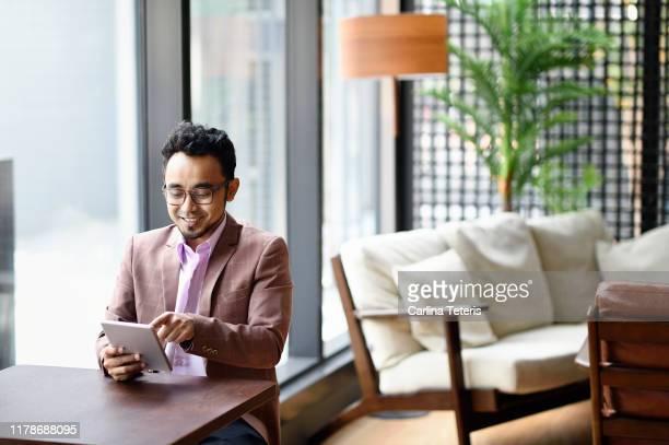 malay man working on a tablet in a co-working office - solo un uomo di età media foto e immagini stock