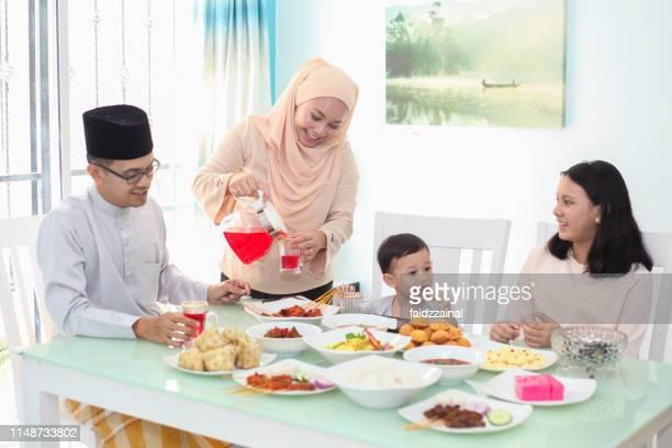 a malay muslim family having hari raya aidilfitri/ eid-ul-fitr meals - hari raya celebration stock pictures, royalty-free photos & images
