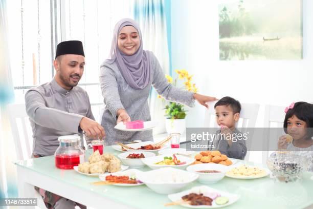 a malay muslim family having hari raya aidlfitri/ eid-ul-fitr meals - eid mubarak stock pictures, royalty-free photos & images