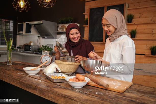 a malay muslim family of mother and daughter baking for hari raya aidilfitri/ eid-ul-fitr - modest clothing stock pictures, royalty-free photos & images
