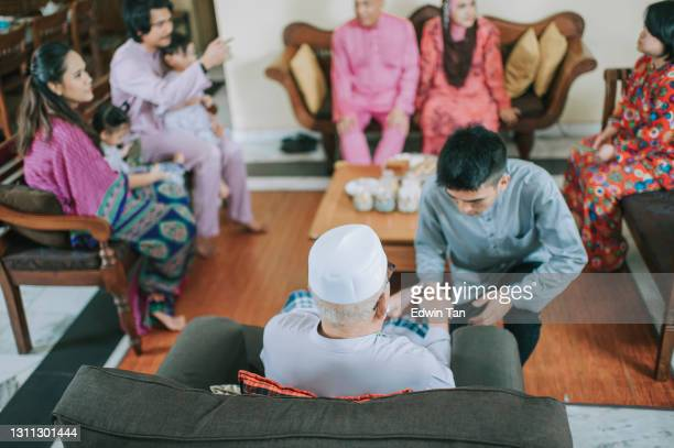 malay muslim son in traditional costume showing apologize gesture to his father during aidilfitri celebration  malay family at home celebrating hari raya - religious celebration stock pictures, royalty-free photos & images