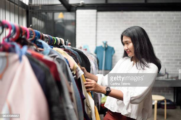 malay woman browsing through a rack of clothes in a studio - clothes rack stock pictures, royalty-free photos & images