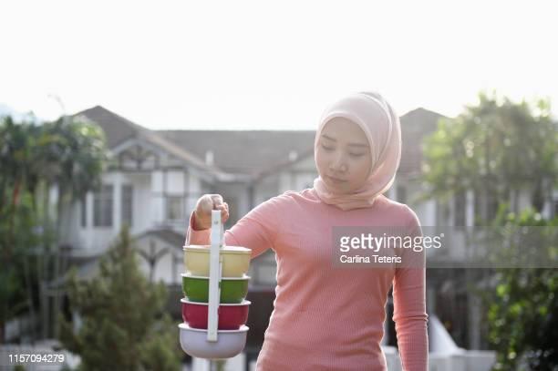 Malay woman carrying a tingkat