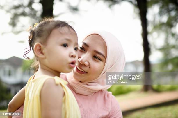 malay woman holding her young daughter in a park - muslim mother stock pictures, royalty-free photos & images