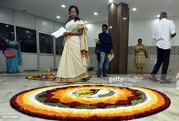 Malayali community members decorate a giant Pookalam a rangoli made by using flowers of several colours to welcome Bhagwan Mahabali to mark the Onam...