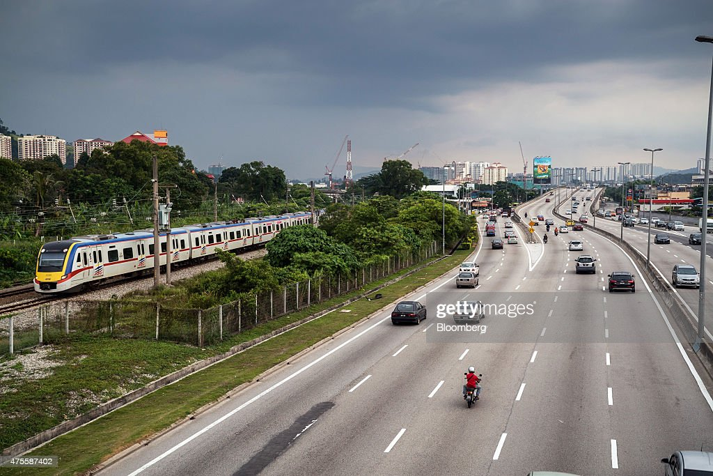 A Malayan Railways Ltd. train operated by KTM Bhd. travels along railway tracks as vehicles drive along a highway in Petaling Jaya, Selangor, Malaysia, on Wednesday, May 27, 2015. Malaysia's ringgit fell for a sixth day on June 1, in the longest stretch of losses since 2013 as falling oil prices weigh on the nation's finances. Photographer: Sanjit Das/Bloomberg via Getty Images