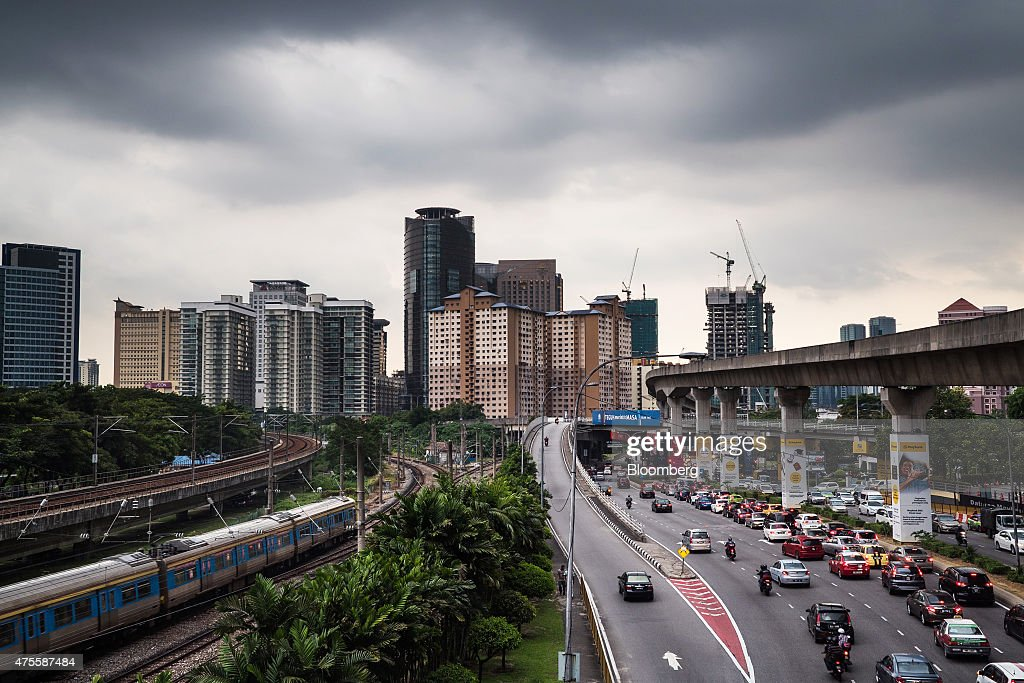 A Malayan Railways Ltd. train operated by KTM Bhd. travels along railway tracks as vehicles drive along a highway in Kuala Lumpur, Malaysia, on Wednesday, May 27, 2015. Malaysia's ringgit fell for a sixth day on June 1, in the longest stretch of losses since 2013 as falling oil prices weigh on the nation's finances. Photographer: Sanjit Das/Bloomberg via Getty Images