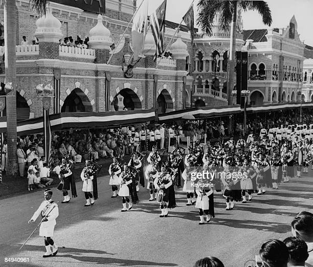 Malayan troops march past the Secretariat in Kuala Lumpur Malaya during celebrations of the Federation of Malaya's independence within the...