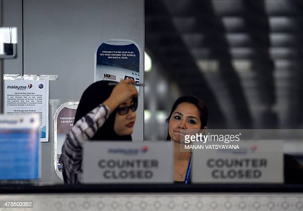Malaysia Airlines employees stand behind a closedcounter at the departure terminal of the Kuala Lumpur International Airport in Sepang on June 1 2015...