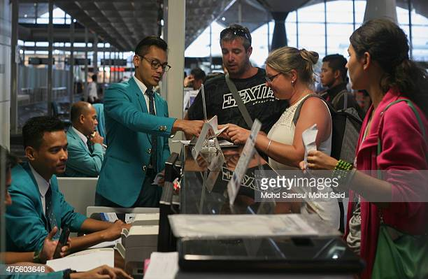 Malaysia Airlines staff help customers at the checkin counter inside the Kuala Lumpur International Airport on June 2 2015 in Sepang Malaysia Chief...