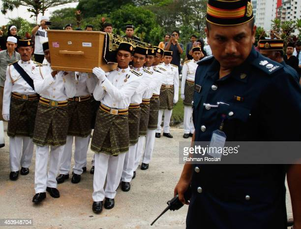 Malaysia Army personnel carry the coffin of Dora Sheila Kassim one of the victim of MH17 in the Bukit Kiara cemetery on August 22 2014 in Kuala...