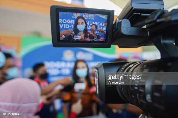 Malaysia Olympic artistic gymnast Farah Ann Abdul Hadi is seen through a video camera screen as she fields questions during a press conference after...
