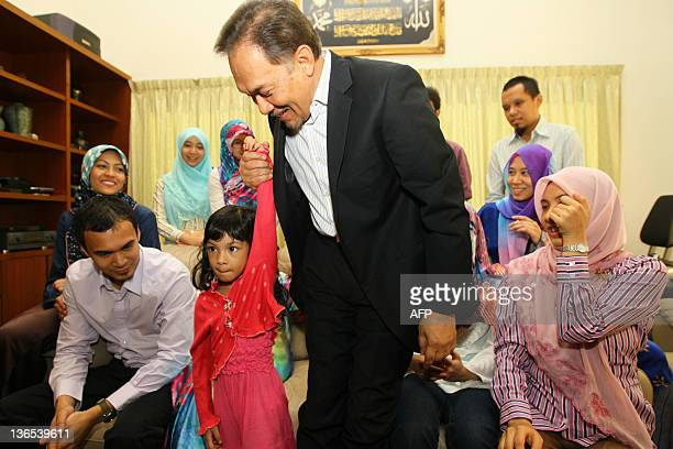 Malaysia opposition leader Anwar Ibrahim holds the arm of his grand daughter grand daughter Raja Safiyah at their home in Kuala Lumpur on January 8...