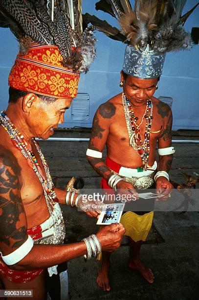 Malaysia Sarawak Kuching Iban Tribe Chief and Warrior Look At Polaroid From Cruise Ship Passenger