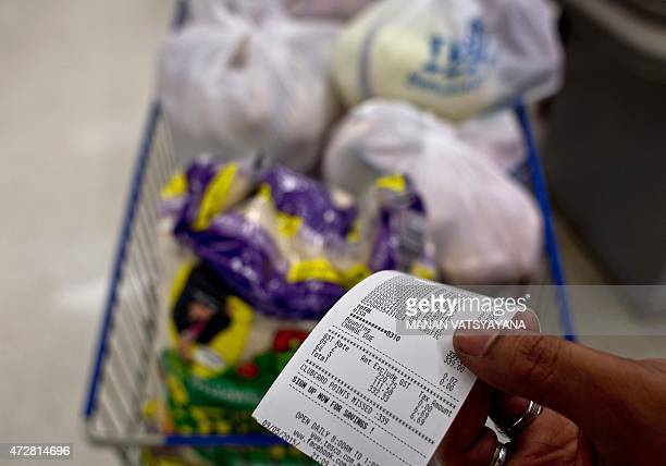 Malaysiaeconomypoliticstax FOCUS by M Jegathesan In this picture taken May 9 a customer poses as he shows his grocery receipt with the added...