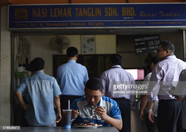 Malaysiafoodlifestylecuisine FEATURE by Satish Cheney In this picture taken March 25 2015 a Malaysian man eats a plate of popular Nasi Lemak dish at...