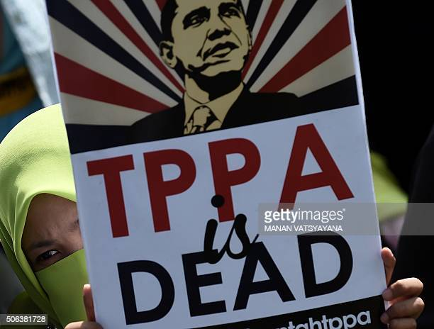 A Malaysian activist holds a placard denouncing the USled TransPacific Partnership Agreement during a protest in Kuala Lumpur on January 23...
