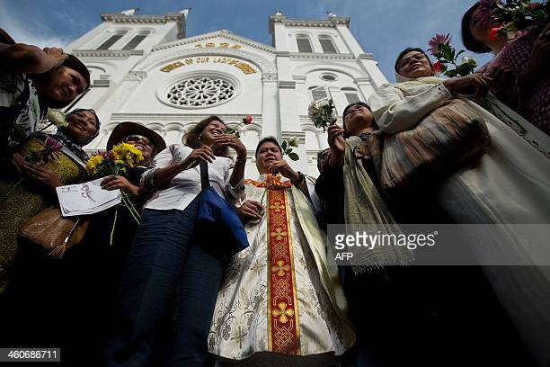 Malaysian activists pose for pictures as they hold flowers with a Catholic priest Michael Chua in front of the Church of Our Lady of Lourdes during a...