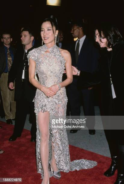 Malaysian actress Michelle Yeoh, wearing a full-length silver evening gown, attends the Los Angeles premiere of 'Tomorrow Never Dies', held at the...