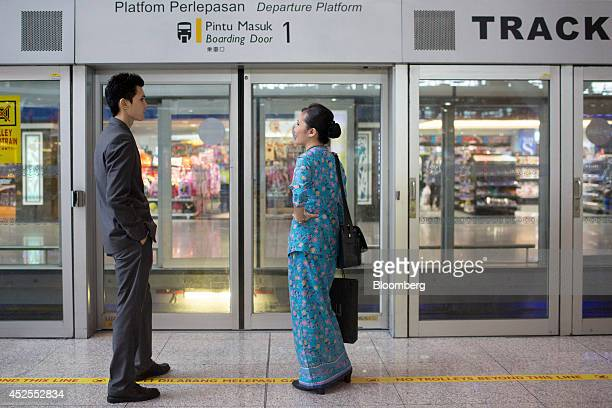 A Malaysian Airline Systems Bhd flight attendant right stands at a train platform at Kuala Lumpur International Airport in Sepang Malaysia on Tuesday...