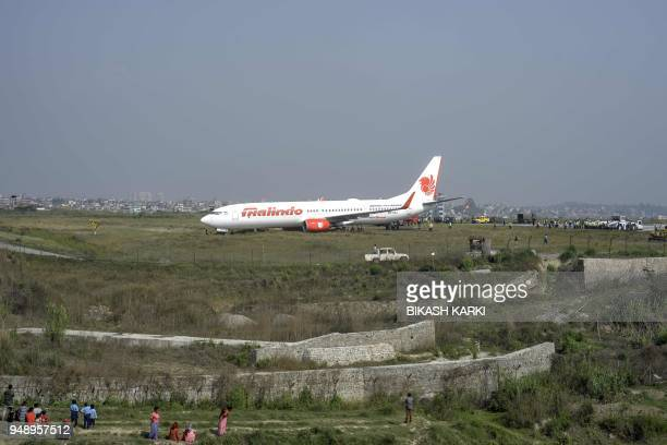 A Malaysian airliner is pictured beyond the runway at the international airport in Kathmandu on April 20 after it skidded off the runway following an...