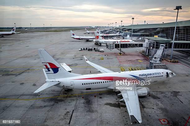 Malaysian Airlines Bhd and Malindo Airways aircraft stand on the tarmac at Kuala Lumpur International Airport in Sepang Selangor Malaysia on Tuesday...