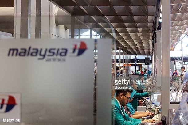 Malaysian Airlines Bhd ground staff work at checkin counters at Kuala Lumpur International Airport in Sepang Selangor Malaysia on Tuesday Jan 17 2017...