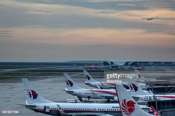 Malaysian Airlines Bhd Malindo Airways and AirAsia Bhd aircraft stand on the tarmac at Kuala Lumpur International Airport in Sepang Selangor Malaysia...