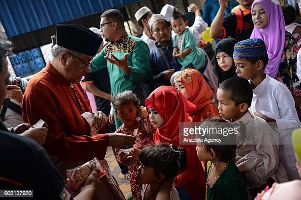 Malaysian Ambassador to Cambodia Dato' Sri Haji Hasan Malek give gifts to children outside the prayer hall during EidAlAdha in Phnom Penh Cambodia on...
