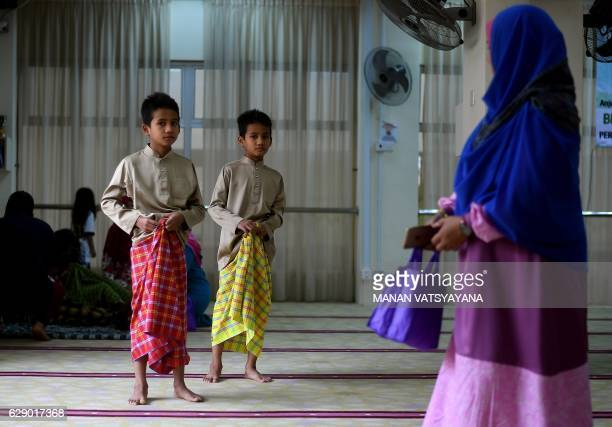 Malaysian boys leave after taking part in a mass circumcision ceremony at the Bandar Tun Hussein Onn mosque in Kuala Lumpur on December 11 2016 Young...