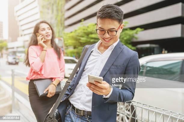 Malaysian business people with smart phones in Kuala Lumpur