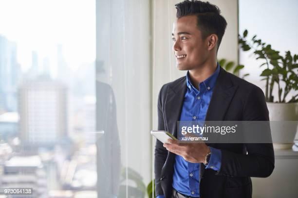 hombre de negocios malasio mirando en la ventana con el teléfono móvil en la oficina - malasia fotografías e imágenes de stock