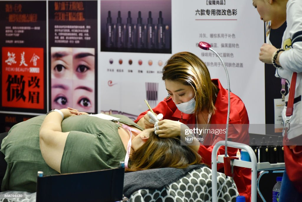 Malaysian Chinese buyer gets her eyebrow tattoo from an exhibitor during the Beauty Expo 2017 on October 6, 2017 at Kuala Lumpur Convention Centre, Malaysia. Beauty Expo 2017 is the highly anticipated annual event in Malaysia for all beauty professionals of the industry. Participants with over 200 international and local exhibiting companies from 25 partcipating countries including South Korea, Japan, China and Thailand.