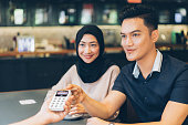 young malaysian couple is paying using
