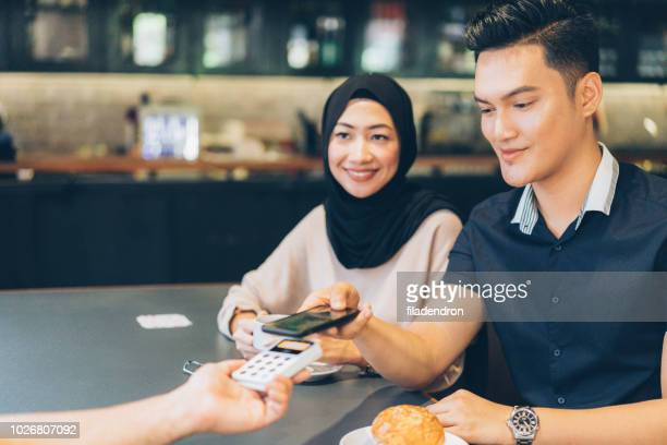 malaysian couple is paying using smart phone in the cafe - money transfer stock pictures, royalty-free photos & images