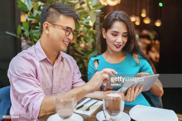 Malaysian couple looking into digital tablet in Kuala Lumpur Cafe