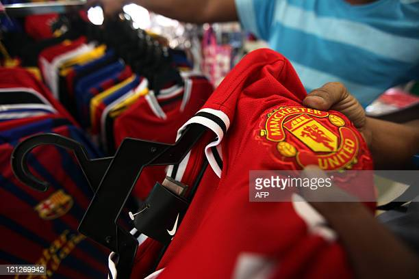 A Malaysian customers checks the logo of English football club Manchester United on a jersey before a purchase at a roadside shop in Kuala Lumpur on...
