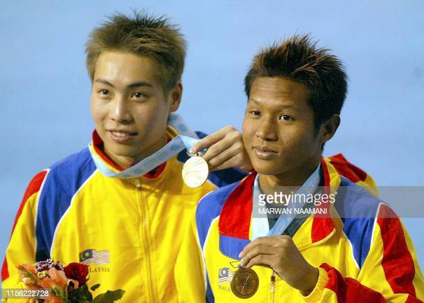 Malaysian divers Ken Nee Yeoh and Roslan Rossharisham show off their bronze medals following the final of the men's 3m sychronized dive event 09...