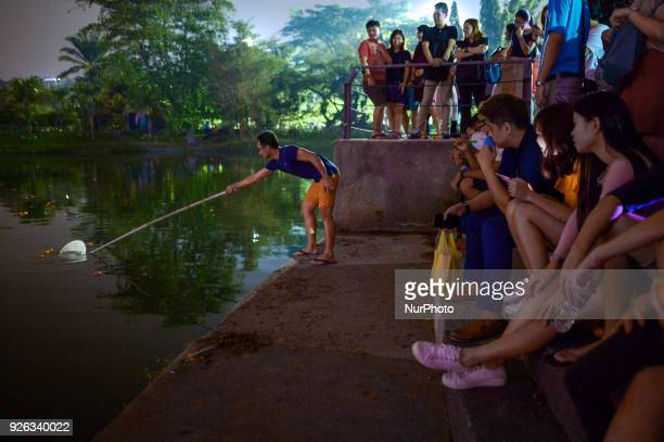 Malaysian ethnic Chinese collects mandarin from the lake after being thrown by Chinese women marking the end of Chinese New Year celebrations in...