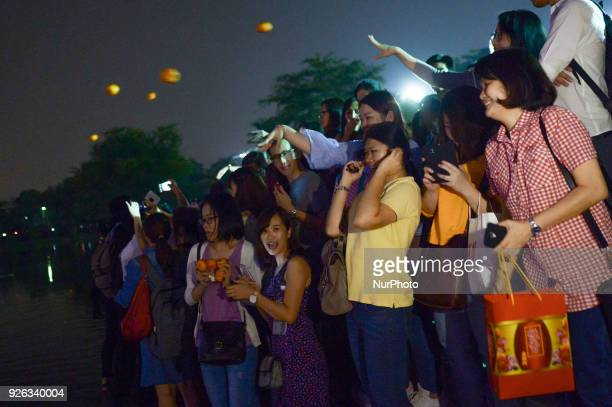 Malaysian ethnic Chinese women gather at a park as they throw mandarin orange written with their wishes and phone number into the lake marking the...