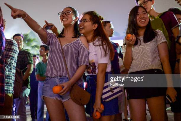 Malaysian ethnic Chinese women gather nearby a lake before throwing mandarin orange written with their wishes and phone number into the lake marking...