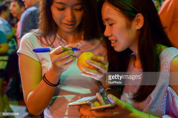 Malaysian ethnic Chinese women write their wishes and phone number on the mandarin orang before throwing into the lake marking the end of Chinese New...