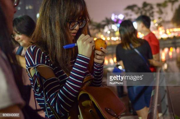 Malaysian ethnic Chinese women writes her wishes and phone number on the mandarin orang before throwing into the lake marking the end of Chinese New...