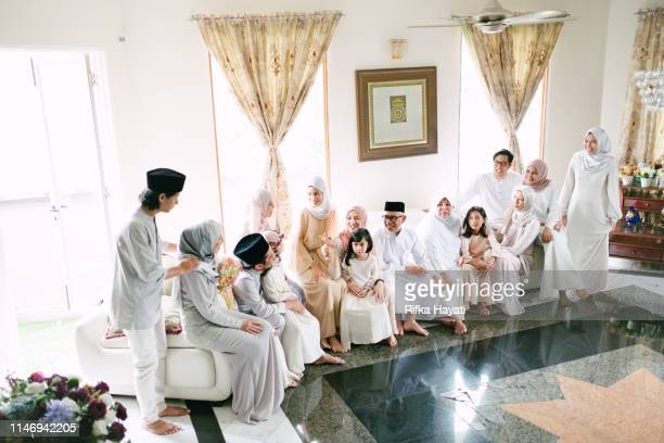 malaysian family celebrating hari raya eid mubarak at home - ceremony stock pictures, royalty-free photos & images