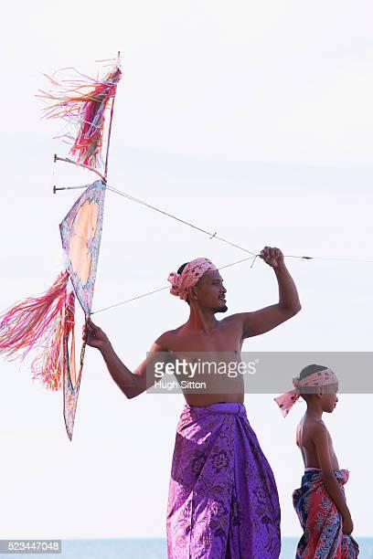 malaysian father and son flying traditional handmade kite on beach - hugh sitton stockfoto's en -beelden