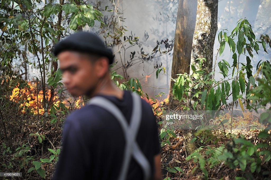 A Malaysian fireman stands next to a bushfire in Taman Bukit Melawati park in Kuala Lumpur on February 18, 2014. There were 312 bush fires reported nationwide on February 12 in just 24 hours during a dry spell this month in Malaysia, local media reported.