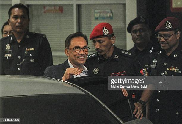 Malaysian former opposition leader Anwar Ibrahim is escorted by prison officers near the court lockup after his hearing in sodomy case on October 12...